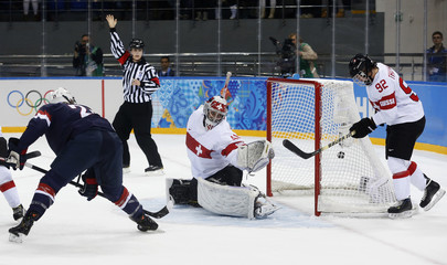 Team USA's Knight scores on Switzerland's goalie Schelling as Switzerland's Thalmann reacts during the first period of their women's preliminary round hockey game at the Sochi 2014 Winter Olympic Games