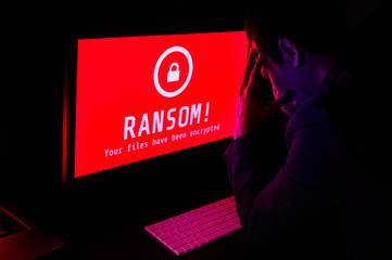 Computer screen with ransomware attack file encrypted alerts in red and a man in suit get stress in a dark room, ideal for online security failure and digital crime, long exposure selective focus