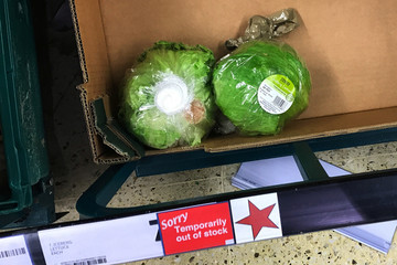"""Remaining iceberg lettuces are seen next to a sign reading """"Temporarily out of stock"""" in a supermarket in London"""