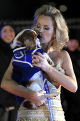 Amanda Holden poses on the red carpet with a dog attending the Battersea Dogs and Cats Home's 150th year 'Collars and Coats Gala Ball' in London