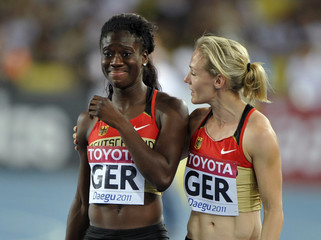 Kwadwo of Germany is consoled by Tschirch after dropping the baton on the first hand off during their women's 4x100 metres relay heat at the IAAF World Championships in Daegu
