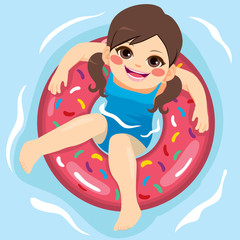 Girl looking up with inflatable rubber ring at swimming pool