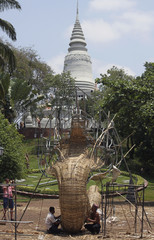 A tourist takes a photo as artists make a serpent statue out of bamboos in Phnom Penh