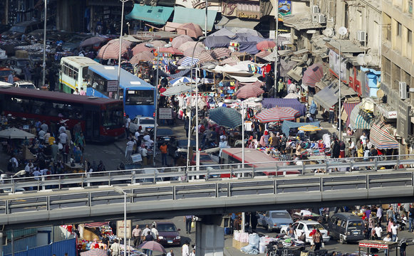 People are seen at a market amidst a traffic jam in downtown Cairo