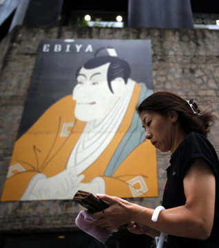 Woman holding a wallet walks past an advertisement poster in the style of a traditional Japanese painting, outside a restaurant in Tokyo