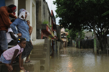 Residents observe floodwaters from tropical storm Chantal in Santo Domingo