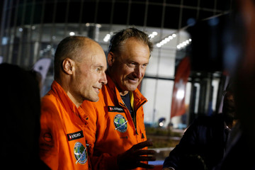Pilot Andre Borschberg and Bertrand Piccard gesture after their arrival on Solar Impulse 2, a solar powered plane, at an airport in Abu Dhabi, UAE