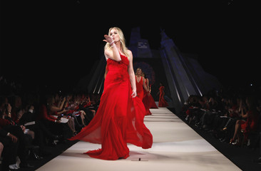 Actress Rebecca Romijn presents a dress by designer Marchesa for the Heart Truth's Red Dress Fashion Show in New York