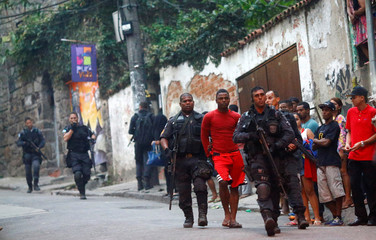 Police officers arrest a suspected drug dealer after a shootout during a police operation at Pavao-Pavaozinho slum in Rio de Janeiro