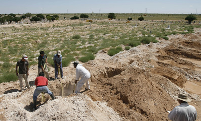 Workers bury a coffin at the San Rafael cemetery on the outskirts of Ciudad Juarez