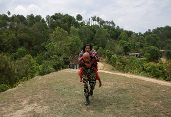 A Nepal Army personnel carries an injured woman to a helicopter following Saturday's earthquake in Sindhupalchowk