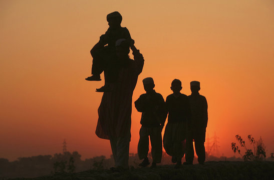 A Muslim man and children are silhouetted against the setting sun on their way to a mosque in Jammu
