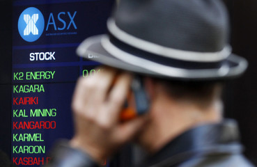 Man talks on a cellular phone while watching indicator boards at the Australian Stock Exchange in Sydney shortly after the local market opened