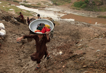 A girl carries her laundry after washing it in a polluted stream in a slum on the outskirts of Islamabad