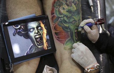 Artist works on a tattoo on the leg of a man, next to an iPad displaying the drawing, during the third International Tattoo Festival in Sao Paulo