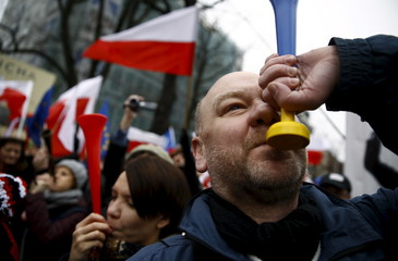 People blow horns as they take part in a march demanding their government to respect the country's constitution in Warsaw