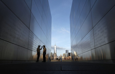 A man touches the wall at the 9-11 Empty Sky memorial across from New York's One World Trade Center at Liberty State Park in Jersey City, New Jersey