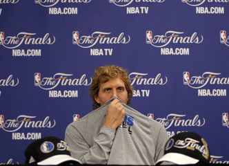 Dallas Mavericks Dirk Nowitzki of Germany, who has flu, wipes his nose during an interview for the NBA Finals basketball series against the Miami Heat in Dallas