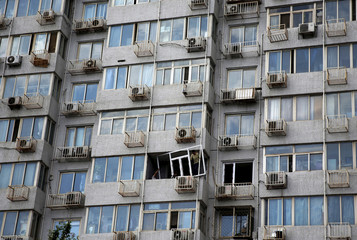 Workers install a window frame on an apartment in Beijing, China