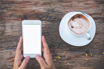 Mockup image of white mobile phone with blank screen and hot chocolate on vintage wooden table in cafe