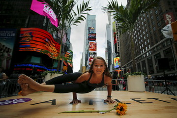 A young participant makes a pose during an event where people practice yoga in Times Square as part of a Summer Solstice celebration on International Yoga Day in New York