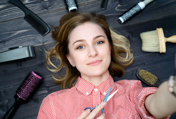 Selfie photo of  happy smiling young woman in plaid shirt with scissors in hand and hairdresser tools among her