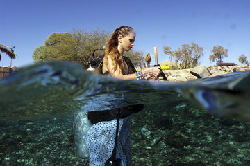 A model prepares to dive in the Red Sea before an underwater photo shoot, in Eilat
