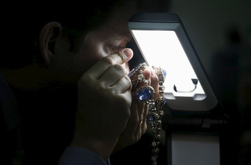 An appraiser from Sotheby's examines the jewellery of former Philippine first lady Imelda Marcos in Manila