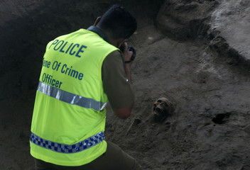 A police officer takes a picture of a human skull at a construction site in the former war zone in Mannar