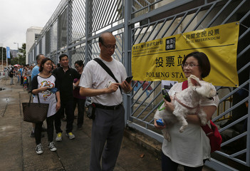 A voter carries her dog as she joins others lining up outside a polling station during an unofficial referendum in Hong Kong