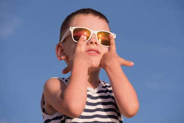 happy little kid wearing sunglasses and striped shirt on blue sky background