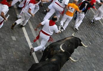 Runners sprint alongside Juan Pedro Domecq fighting bulls at Plaza Consistorial during seventh running of bulls at San Fermin festival in Pamplona