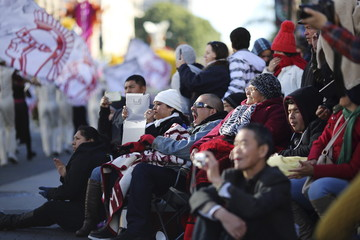 People who stayed overnight on the sidewalk to have a curbside view watch the 127th Rose Parade in Pasadena, California.