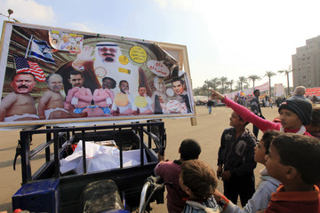 Children look at a poster referring to Middle Eastern and north African leaders, and former leaders, in Tahrir square in Cairo
