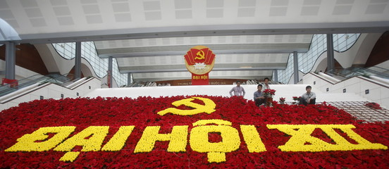 People arrange flowers used to set up a decoration with the Communist logo promoting the upcoming 12th national congress of the Vietnam's Communist Party at the national convention center, the congress venue, in Hanoi