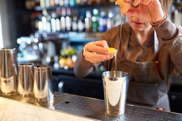 bartender with shaker preparing cocktail at bar