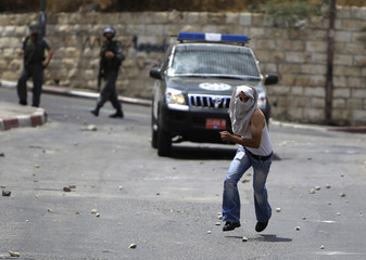 A Palestinian runs away after throwing stones at the Israeli security forces during clashes outside the old city in Jerusalem