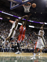 Los Angeles Clippers guard Fortson drives for a lay-up between Utah Jazz guard Watson and forward Miles during first half their NBA basketball game in Salt Lake City