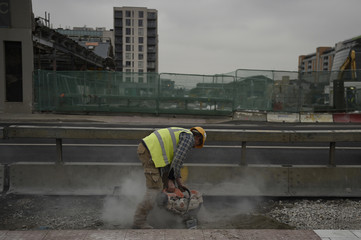 A construction worker uses a power tool in the Capital Dock area of Dublin