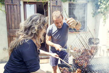 nice mature couple preparing grilled meat for friends outdoor