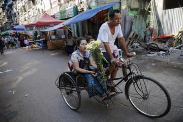 Woman rides a trishaw in downtown Yangon