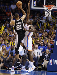 Oklahoma City Thunder center Kendrick Perkins reaches up to block a shot by San Antonio Spurs forward Tim Duncan in the second half of their NBA basketball game in Oklahoma City.