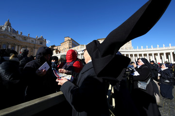 "A nun distributes books titled ""Icons of Mercy"" donated by Pope Francis to the faithful on Epiphany day in Saint Peter's Square at the Vatican"