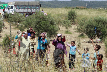 Syrians shout slogans in favour of Turkey as they wait to cross into Turkey, on the Syrian side of the border, near Turkish village of Guvecci