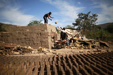 Worker standing on a pile of bricks receives bricks from another worker at a brick factory in Tixtla, on the outskirts of Chilpancingo, in the Guerrero state