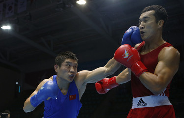 China's Zhang fights with Kazakhstan's Niyazymbetov during their men's light heavy (81kg) quarterfinal boxing match at Seonhak Gymnasium during the 17th Asian Games in Incheon