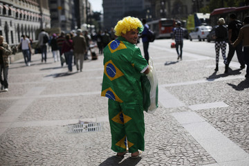 Do Prado walks along a street wearing clothes made with Brazilian flags, in preparation for the 2014 World Cup, in Sao Paulo