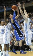 Duke University's Austin Rivers goes to the basket against University of North Carolina players John Henson, Reggie Bullock, and Tyler Zeller in Chapel Hill