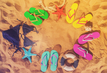 Summer beach fun - frame on sand with colorful sandals and swimming suits, retro toned