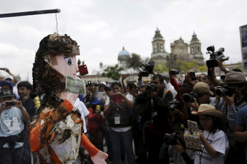 Media members take pictures of a figure, representing Guatemalan Vice President Roxana Baldetti, on fire during a demonstration to commemorate International Labour Day in downtown Guatemala City